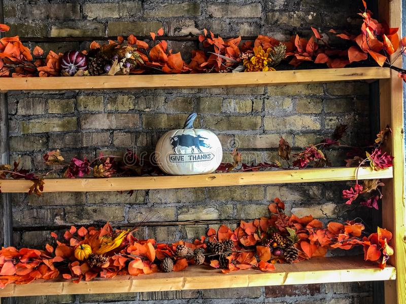 Autumn leaves decoration on shelves by brick wall stock photos