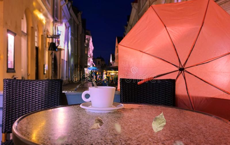 Autumn evening in city street cafe cup of coffee on table rainy night pink umbrella Old Town Of Tallinn. Autumn leaves  evening in city street cafe cup of coffee royalty free stock photo
