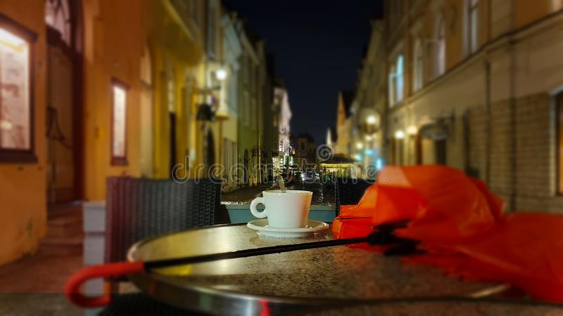 Cup of coffee Autumn evening in city street cafe on table rainy night pink umbrella Old Town Of Tallinn. Autumn leaves  evening in city street cafe cup of coffee royalty free stock images