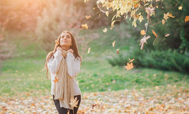 Autumn leaves falling on happy young woman in forest. Portrait of very beautiful girl in fall park royalty free stock photo