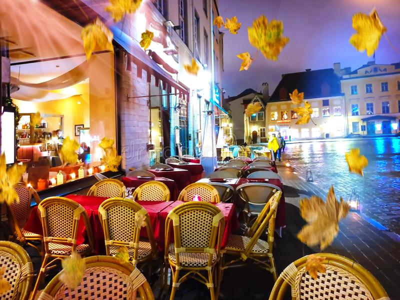 Autumn leaves street cafe tables in Old Town Of Tallinn town square ,evening city lights red tables and chair windows reflection. Autumn leaves street cafe royalty free stock image