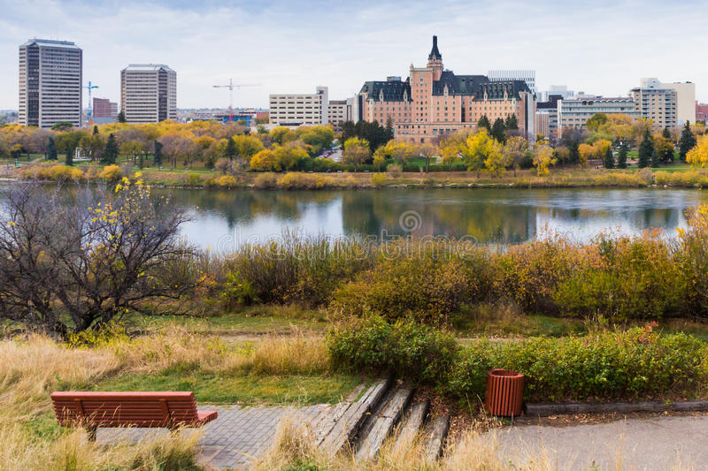 Autumn. Lonely bench by the river with a view of Saskatoon downtown stock photo