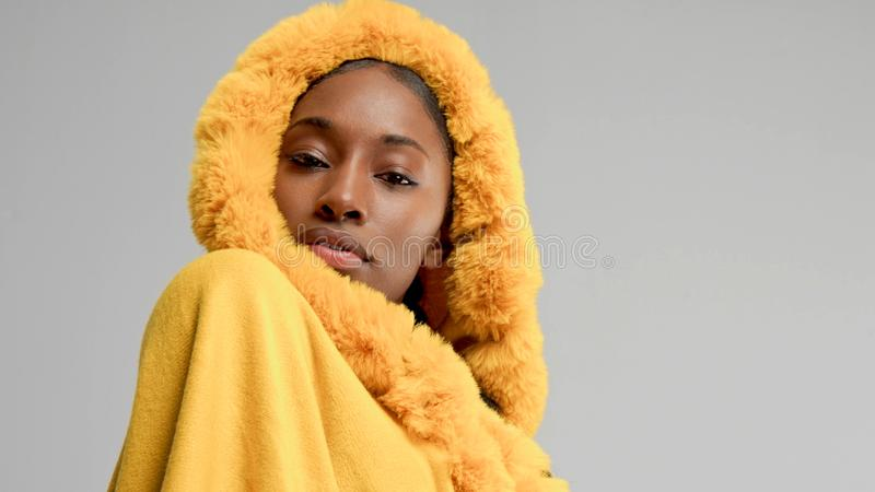 Black moxed race woman in bright yellow outwear poncho on grey royalty free stock image