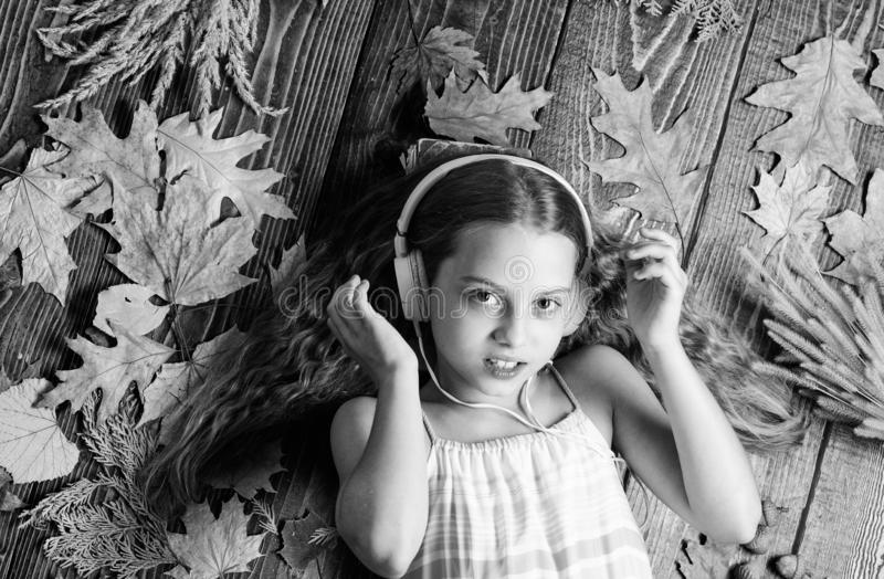 Autumn melody concept. Child listen music relaxing top view. Autumn music playlist. Best songs about fall. Enjoy music. And relax. Happy childhood. Kid girl royalty free stock images