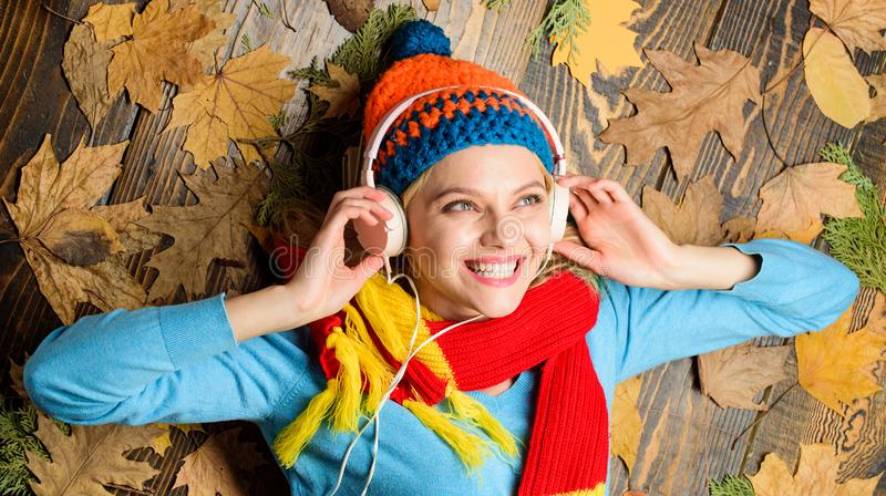 Autumn melody concept. Hipster woman knitted hat and scarf listen music headphones. Fall cozy atmosphere. Fall and royalty free stock image