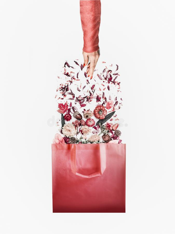 Autumn minimal concept . Shopping bag with autumn flowers and fall leaves arrangement and female hand in red pullover on white stock image