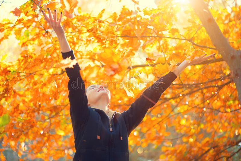 Autumn model girl spinning and laughing in autumnal park, forest, throws colorful leaves. Beautiful Young Woman Having Fun outdoor. S. Raising hands. Falling Red stock photography