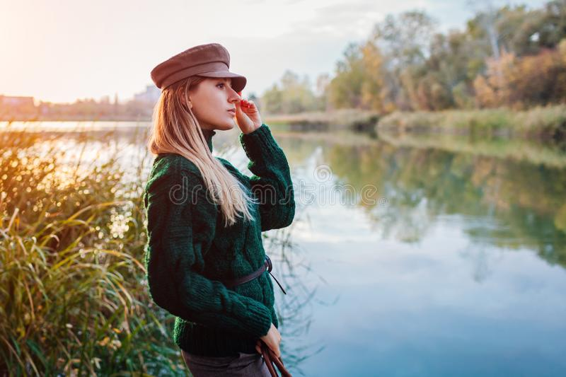 Autumn fashion. Young woman wearing stylish outfit and hat by river. Clothing and accessories royalty free stock photos