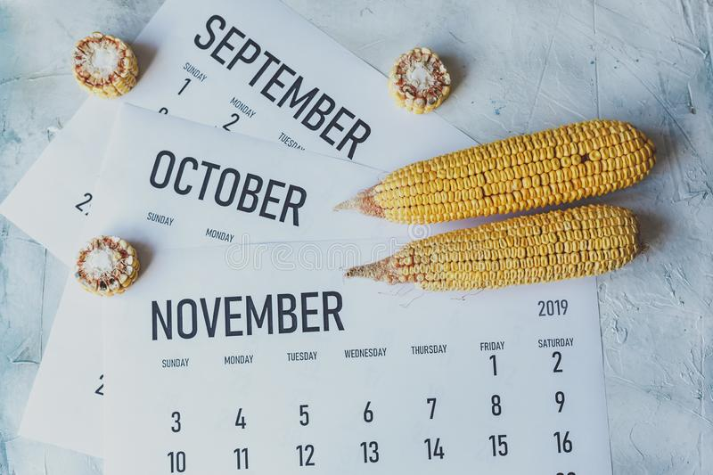 Autumn Months, Fall season concept. Harvest time. Three monthly calendars of September, October and November. Top view to calendars and raw corns stock image
