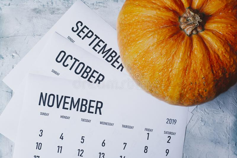 Autumn Months, Fall season concept. Three monthly calendars of September, October and November. Top view to calendars and pumpkin stock images