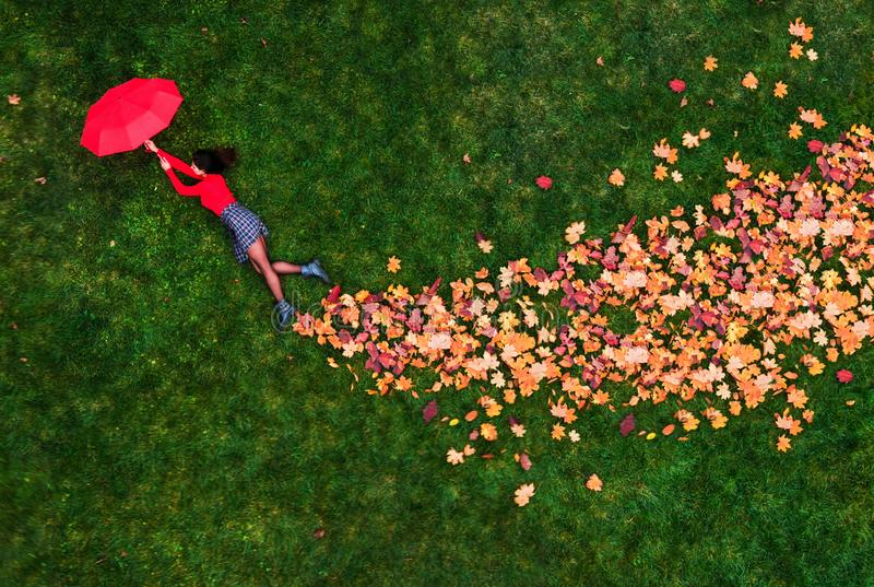Autumn mood. Beautiful young woman on the autumn grass and yellow leaves. Seasonal autumn fashion. Creative picture from above stock photography