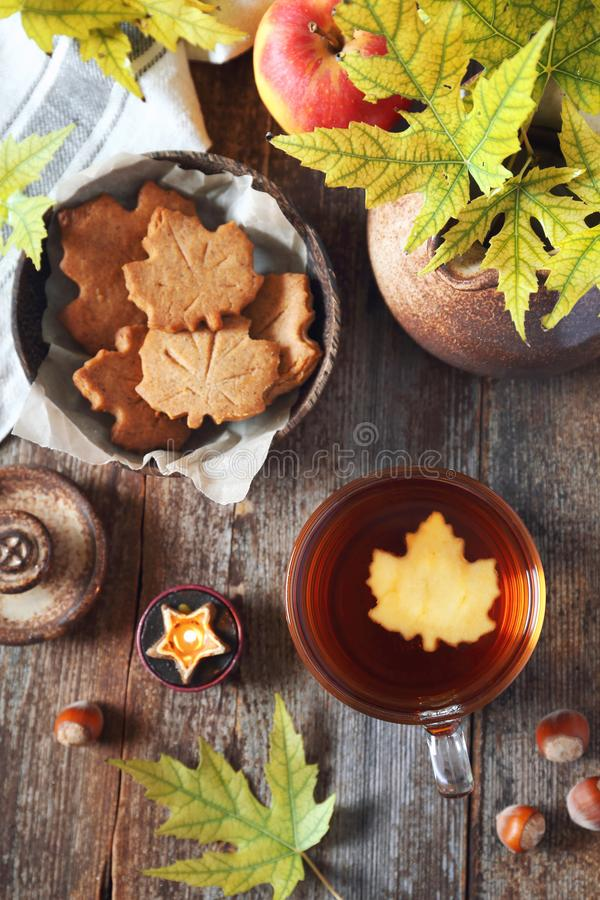 Autumn mood: cinnamon cookies in form of maple leaves, cup of tea, red apple and yellow leaves royalty free stock images