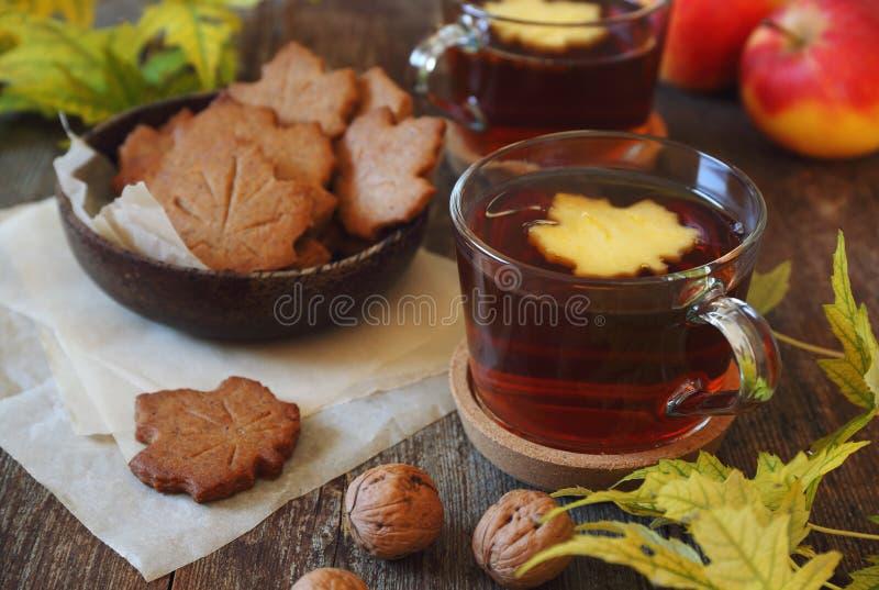 Autumn mood: cinnamon cookies, tea, red apple and yellow leaves stock photo