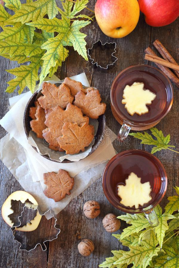 Autumn mood: cinnamon cookies in form of maple leaves, two cups of tea, red apples and yellow leaves royalty free stock image