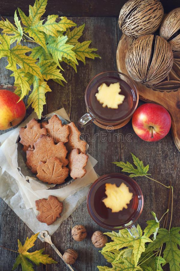 Autumn mood: cinnamon cookies in form of maple leaves, two cups of tea, red apples and yellow leaves stock photos