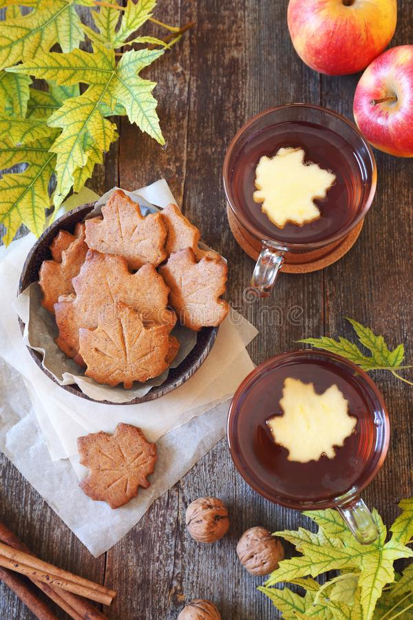 Autumn mood: cinnamon cookies in form of maple leaves, two cups  of tea, red apples and yellow leaves royalty free stock photos