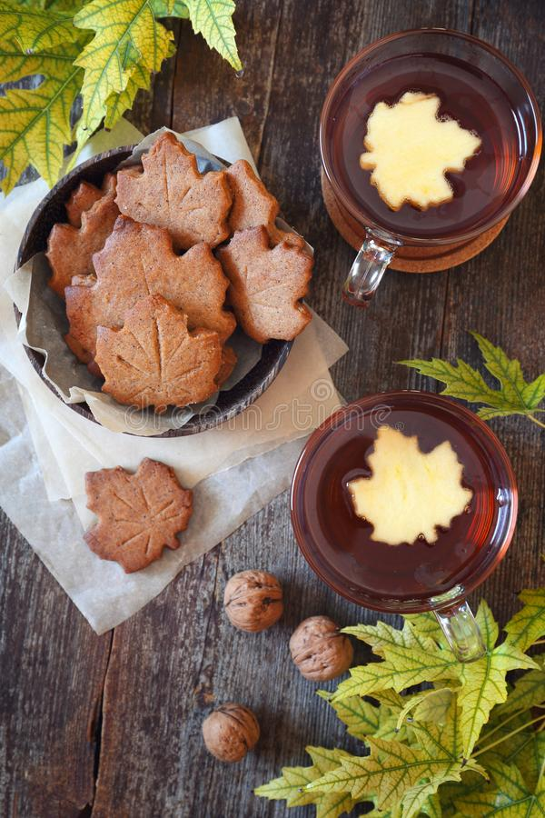 Autumn mood: cinnamon cookies in form of maple leaves, two cups of tea and yellow leaves stock photography