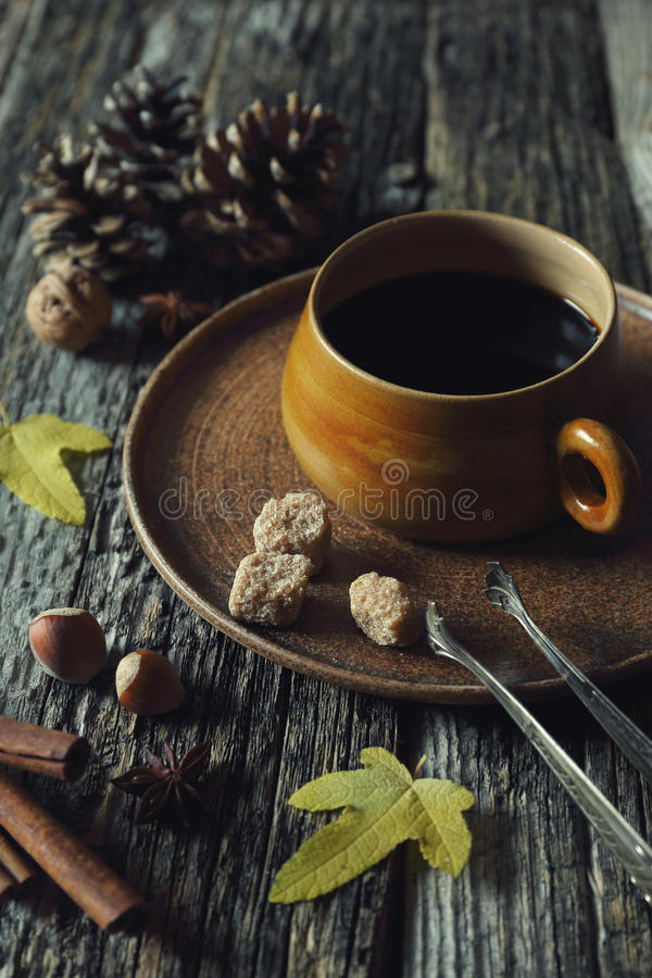 Autumn mood: cup of coffee, nuts and autumn leaves stock image