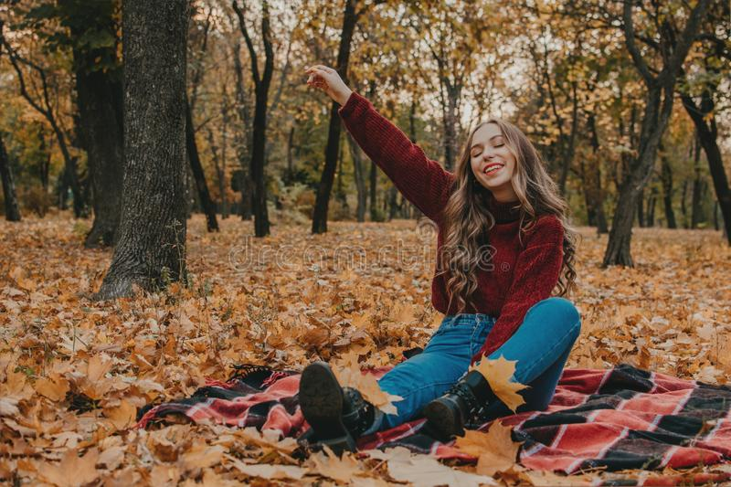 Autumn mood. Fall lifestyle portrait of brunette with long curly hair. Young beautiful Casual joyful woman having fun in fall city royalty free stock photos