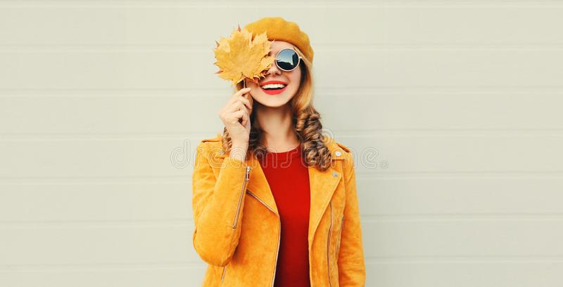 Autumn mood! happy smiling woman holding in her hands yellow maple leaves hiding her eye over gray wall stock photos
