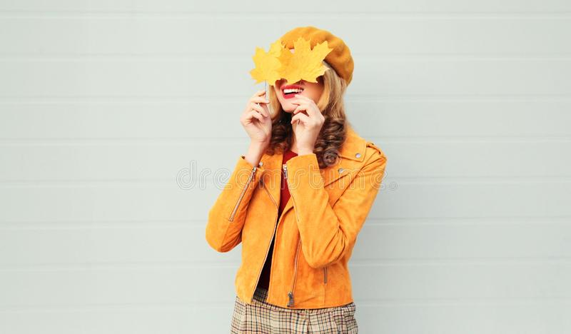 Autumn mood! happy smiling woman holding in her hands yellow maple leaves hiding her eyes over gray wall stock photos