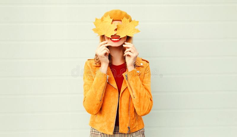 Autumn mood! happy smiling woman holding in her hands yellow maple leaves hiding her eyes over gray wall royalty free stock photo