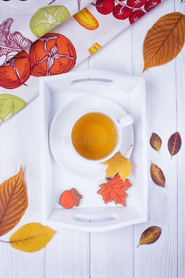 Autumn mood. Herbal tea, gingerbread maple leaf and acorns and dry autumn leaves on a white wooden background stock photo