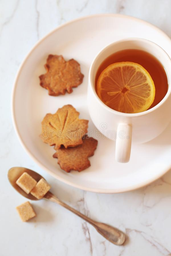 Autumn mood: lemon tea and cinnamon cookie in the form of maple leaf royalty free stock photos