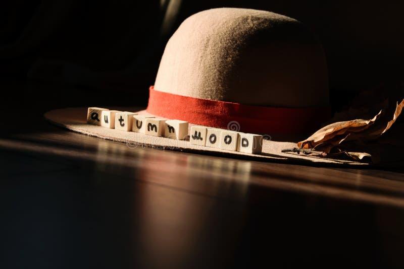 `Autumn mood ` text phrase on female autumn hat stock photo