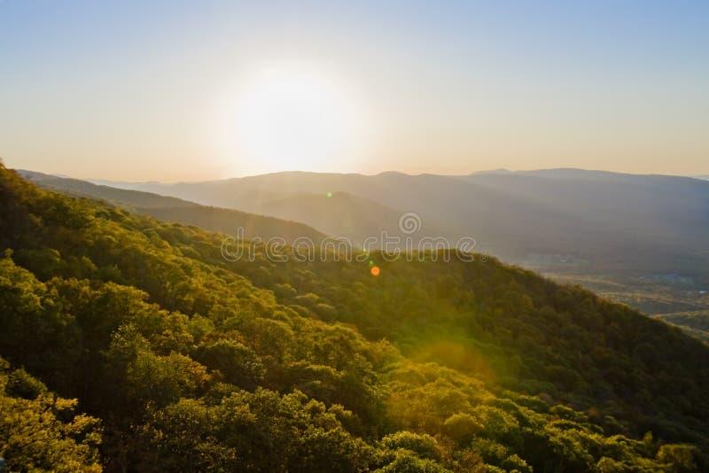 Autumn mountains. Sun falling below autumn colored mountain range royalty free stock photos