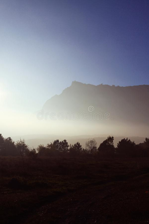 Autumn mountains in the fog and winding road. Sunset. stock photos
