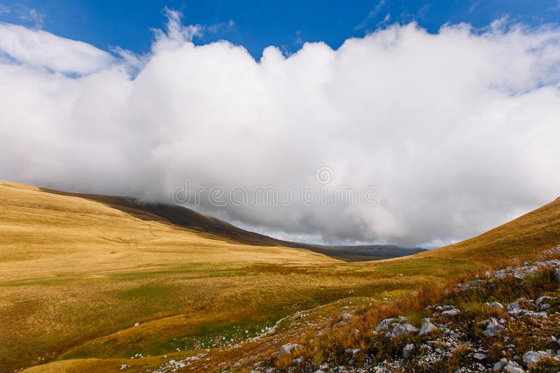 Autumn mountains. Low clouds in the mountains. Big white cloud royalty free stock photos