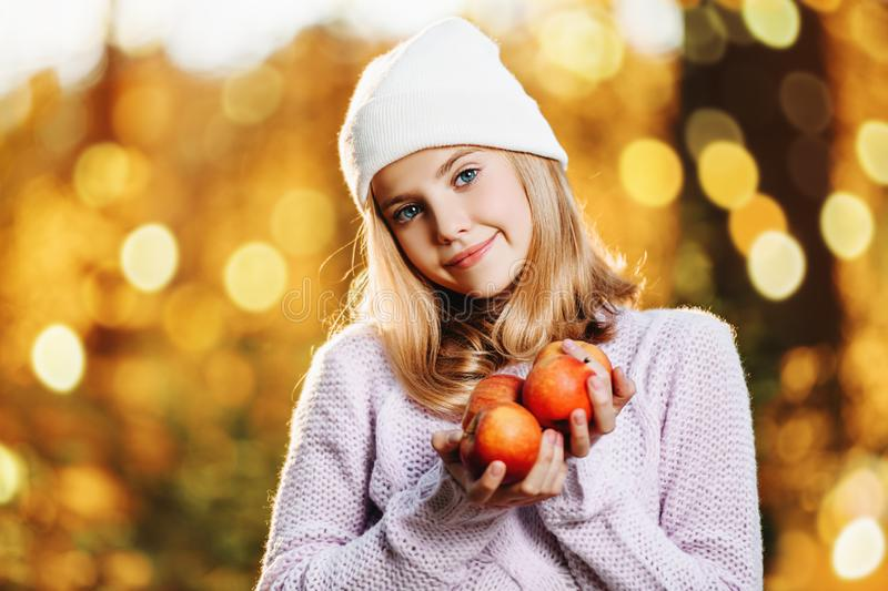 Autumn nature and apples. A pretty young girl with apples. Autumn fashion, beauty. Healthy lifestyle stock photography