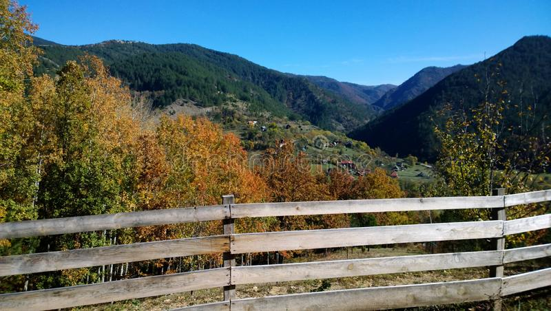 Autumn nature outside the city. A wooden fence, the tops of the mountains, colorful trees royalty free stock photos
