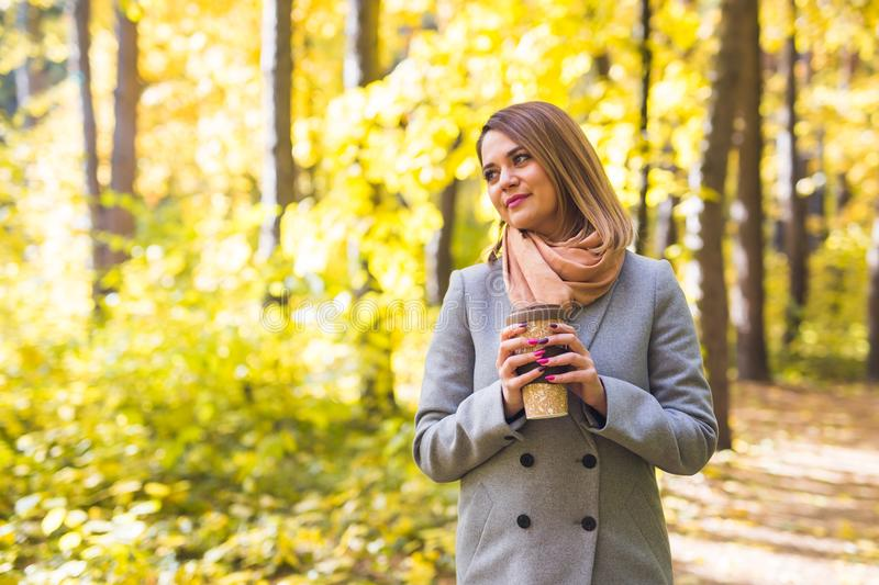 Autumn, nature and people concept - Young beautiful woman in grey coat holding a cup of coffee royalty free stock photo