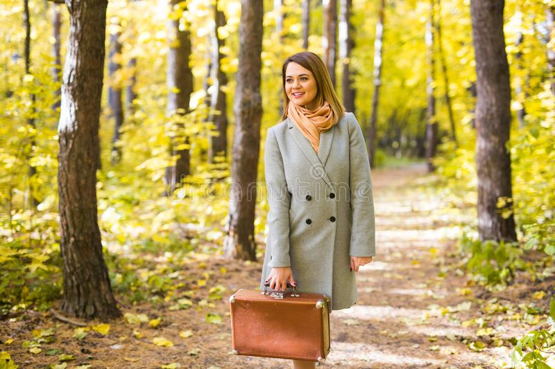 Autumn, nature and people concept - Young beautiful woman walking in park with suitcase stock photo