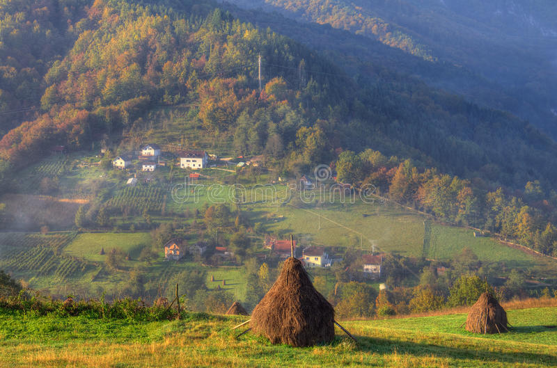 Autumn near Bajina Basta, Western Serbia. Beautiful picture with mountain, farms in the mist, yellow and red forest and haystack in front of the picture royalty free stock image