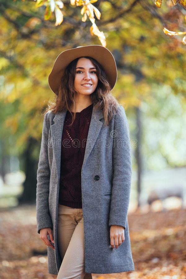Autumn outdoor portrait of happy smile woman in autumn park in cozy coat and hat. Warm sunny weather. Fall concept stock images