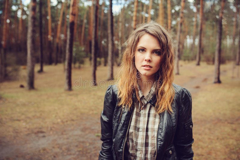 Autumn outdoor portrait of young beautiful woman with natural makeup in leather jacket and plaid shirt. Soft vintage toned stock image