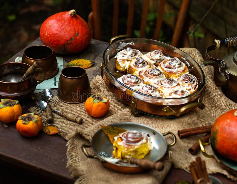 Autumn outdoor still life with homemade pumpkin cinnamon buns in oval glass dish. On wooden table with copper mugs, pumpkins, persimmons, teapot, spoons stock photos