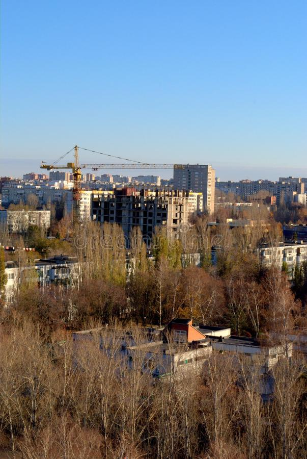 Autumn panorama of the city overlooking the residential building under construction and the tower crane. Autumn panorama of the city of Togliatti overlooking stock image