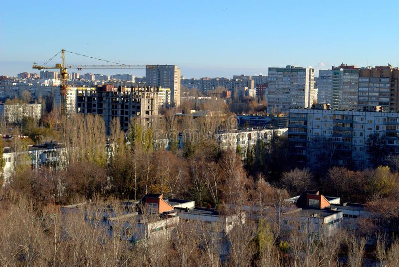 Autumn panorama of the city overlooking the residential building under construction and the tower crane. Autumn panorama of the city of Togliatti overlooking the stock photos