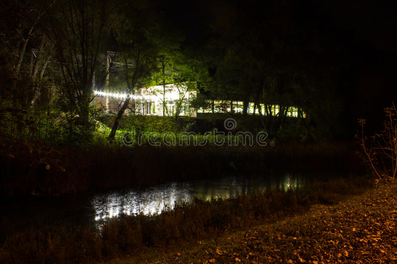 Autumn park at night. Burning building lights reflected in the lake. Background. Autumn park at night. Burning building lights reflected in the lake royalty free stock image