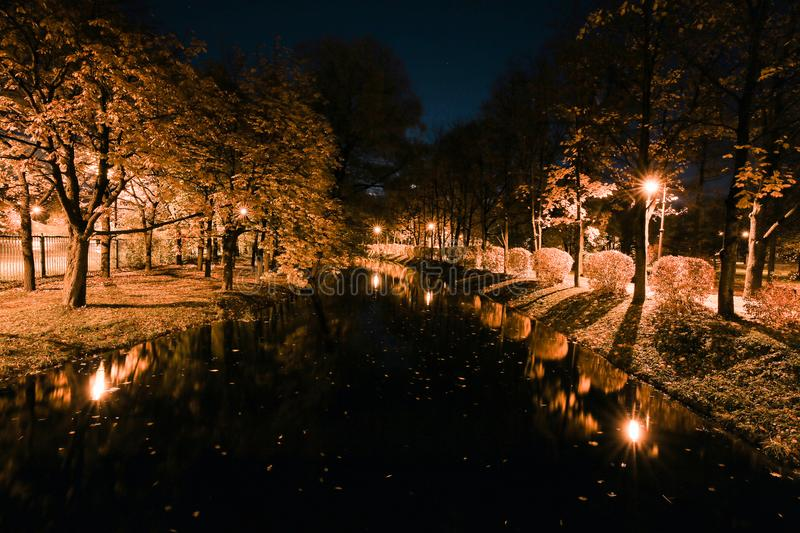 Autumn city park at night. Street lights and trees along the river. Autumn park. Night park. City park at twilight. Trees, river, street lights, light lantern stock image
