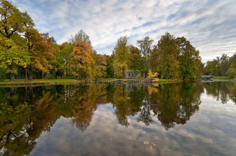 Autumn pond. With red and yellow colored trees next to it royalty free stock photos