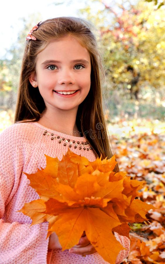 Autumn portrait of adorable smiling little girl child with leav royalty free stock image