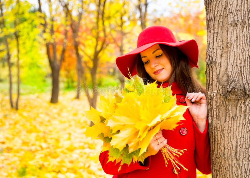 Autumn portrait of beautiful woman over yellow leaves while walking in the park in fall. royalty free stock image