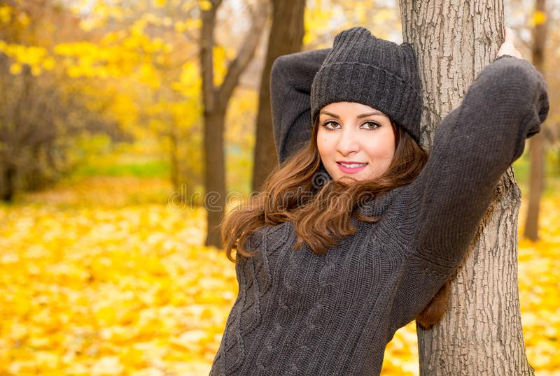 Autumn portrait of beautiful woman over yellow leaves while walking in the park in fall. Positive emotions and happiness concept. royalty free stock photo