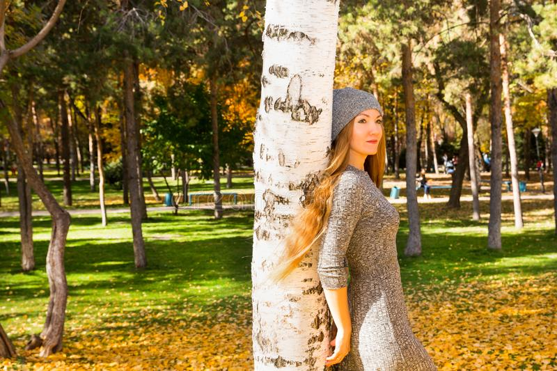 Autumn portrait of beautiful woman over yellow leaves while walking in the park in fall. Positive emotions and happiness concept. stock images
