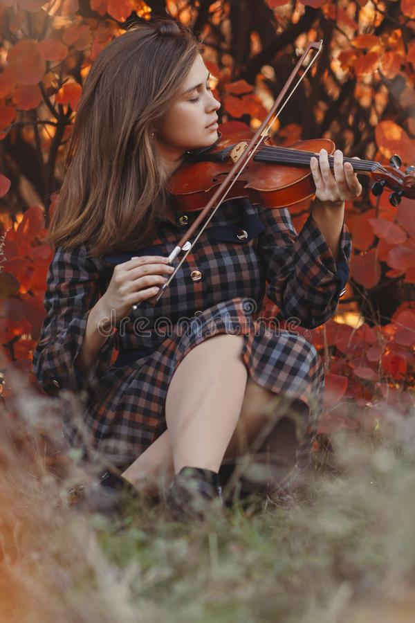 Autumn portrait of beautiful woman sitting on the ground with a violin under chin on a background of red foliage, girl engaged in. Playing a musical instrument royalty free stock image
